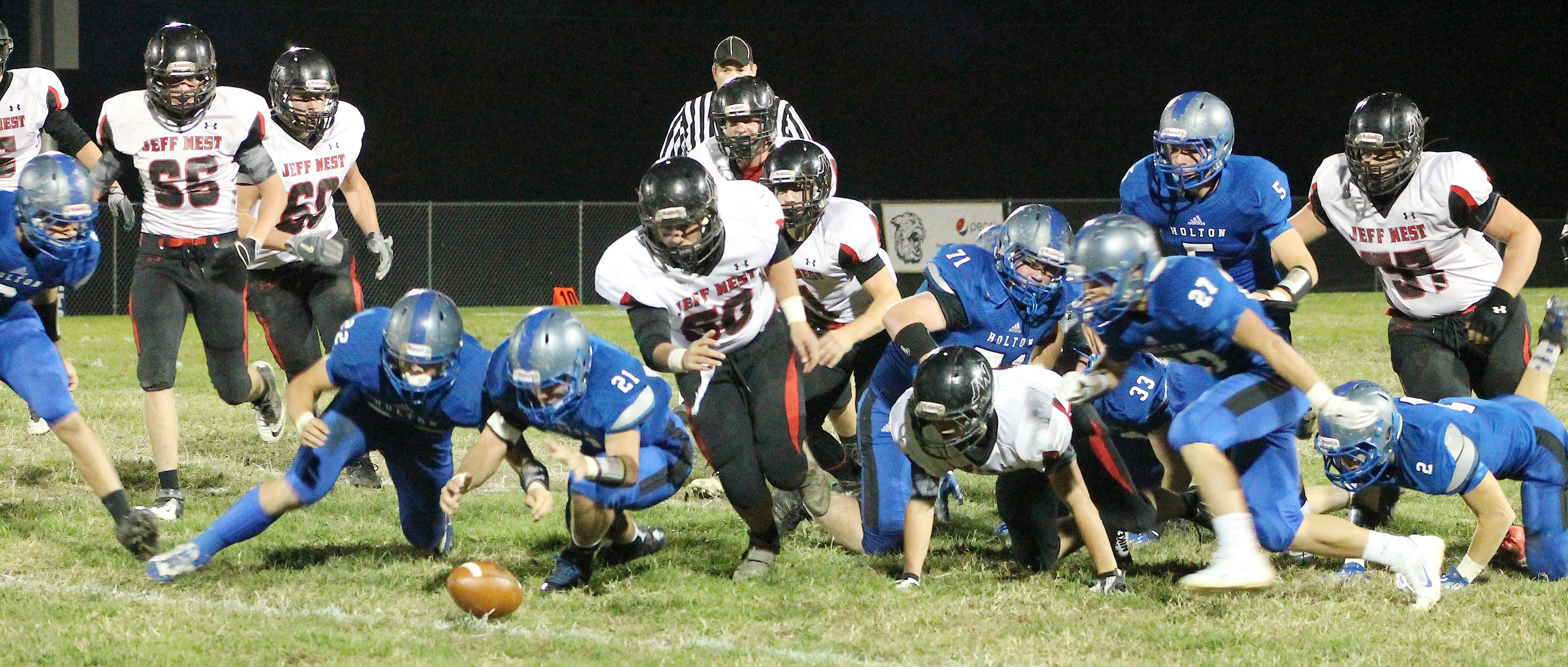 Holton linebackers Indie Allen (lower left) and Mason Barta (lower right) dive for a loose ball early in the game against Jeff West. Barta recovered the football and HHS went on to score on the very next play on the way to a 38-6 victory.