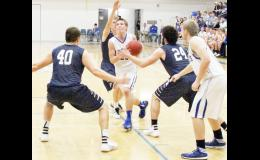 Holton's Bryson Patch (center) stepped through a trio of Sabetha Blue Jay defenders to go for a score, with teammate Aaron Bain (at right) at the ready for a pass. Patch contributed 25 points to the Wildcats' 47-38 victory on Friday. (Photo by Brian Sanders)