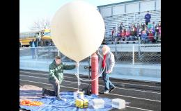 Jackson Heights athletic director Lyle Alley (left) held onto a weather balloon about to be launched while support staffer Huck Keithline (right) filled the balloon with hydrogen Tuesday morning while fifth-graders from Holton and Jackson Heights looked on in anticipation of the launch. (Photo by Brian Sanders)