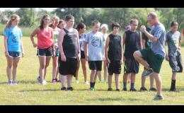 New JHHS cross country head coach Brad Alley (shown above, front right) demonstrates the proper running form to his team at a practice early on this season.
