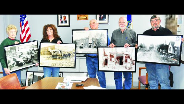 Verlin (center) and Sue (at left) Wichman of Holton presented 19 historic photos of Holton and other county towns to the Jackson County  Commissioners last week. The commissioners agreed to purchase the photos, which will be on display on the Courthouse walls. The commissioners included Janet Zwonitzer (second from left), Bill Elmer (second from right) and Ed Kathrens (right).