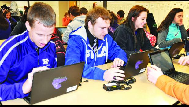 Royal Valley High School sophomores (from left) Lucas Broxterman, Noah Ensley, Maggie Schuetz and Rachael Keehn took a moment to explore their new Chromebook laptops after they were checked out to freshmen and sophomore students on Tuesday morning. The Chromebooks are part of a new one-to-one technology initiative at the school.
