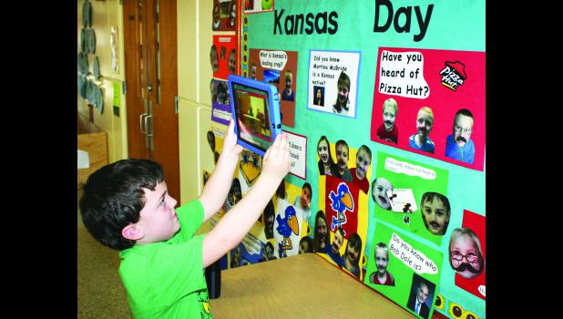 """Sterrett McCauley, a first-grade student at Colorado Elementary School in Holton, used an iPad with an """"augmented reality"""" (AR) app to answer a question about whether country singer Martina McBride is a Kansas native (answer: McBride was born and raised in Barber County). The school is displaying a bulletin board this week that uses AR technology to answer ques¬tions about Kansas people, places and things in honor of Kansas Day, which is Thursday."""