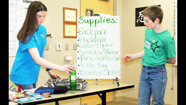 Members of 4-H clubs from Jackson and Nemaha counties participated in the annual 4-H Club Day, held Saturday at Jackson Heights High School. Here, Madeline Montgomery (left) packed a bag for a hike while younger brother Blade Montgomery (right) made suggestions on what to pack during a presentation. The Montgomery kids are members of the Lucky Stars 4-H Club. (Photo by Brian Sanders)