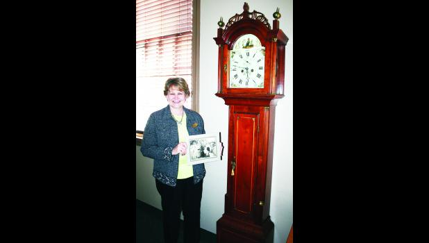 """Beck-Bookman Library employee Gail Schmitz is shown in the photo above with a grandfather clock that dates back to the early 1800s. The clock was donated to the library by the family of a former librarian, Ellen """"Nell"""" Lowell."""