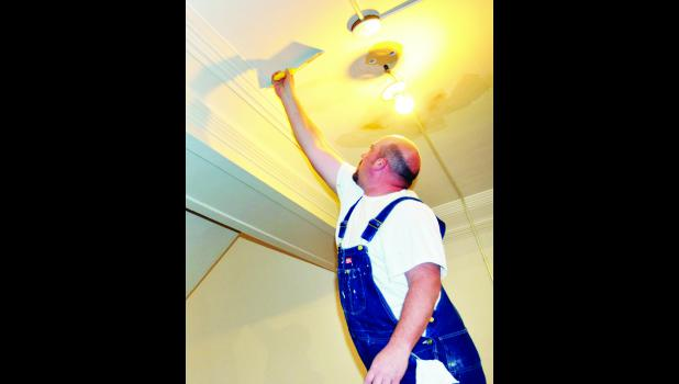 Chad DeMoss of Ken Weigel Painting of Topeka patched some holes in the ceiling on the first floor of the Jackson County Courthouse Tuesday evening before the walls and ceiling were set to be painted.