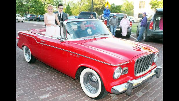 Kelly Shepley (left) and Rieder Bjelland (center) arrived at the prom in the back of a Studebaker convertible owned by Scott Bartlett and driven by Bjelland's father, Eric.