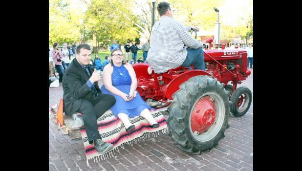 Different modes of transportation were used in getting Holton High School students and their dates to the prom, held Saturday evening at Penny's on the Square. Here, Tim Stauffer (left) and Robyn Potter arrived at the prom on the back of an old Farmall tractor.