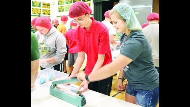 Chase Gigstad (right) — whose efforts brought the FCE program to Jackson Heights — helped Blayne Gibson (center) seal a meal while Grace Bowhay packed a meal for distribution.