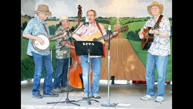 The 26th-annual Prairie Lake Pickin' Party this past weekend featured the music of 15 groups, including Legacy, which took the Prairie Lake stage on Friday evening. Band members — from left to right, Randy Rahberg on banjo, Don Anderson on bass and Jim Rood and Bob Hirt on guitars — said their appearance at this year's Pickin' Party marks the band's 20th appearance at the annual event. (Photo by Brian Sanders)