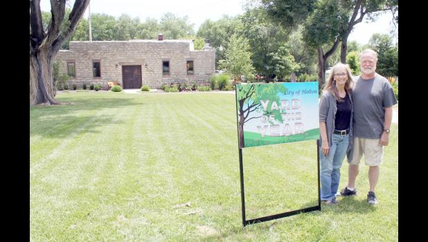 "Gerald (right) and Cheryl Copeland of Holton have been honored with the ""Yard of the Year"" award from Holton's Parks and Recreation Department. The Copelands have owned this property, located in the 100 block of South Iowa Avenue, for about 15 years, most of which the building served as a woodworking shop for Gerald Copeland but was renovated into living space about three years ago. The property also includes a studio space that the Copelands said once served as a gas station. (Photo by Brian Sanders)"