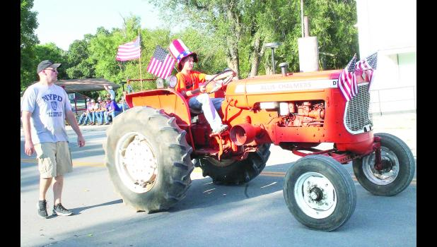 GRAND OLD TRACTOR - Ethan Caviness, shown above, added a patriotic theme to the Allis-Chalmers tractor he drove in the Soldier Parade Saturday evening. Ethan's dad, Andy, shown at the left, followed his son on foot along the parade route. The tractor, a 1967-era D17, Series II, belonged to Ethan's great-grandfather on the Caviness side, it was reported.