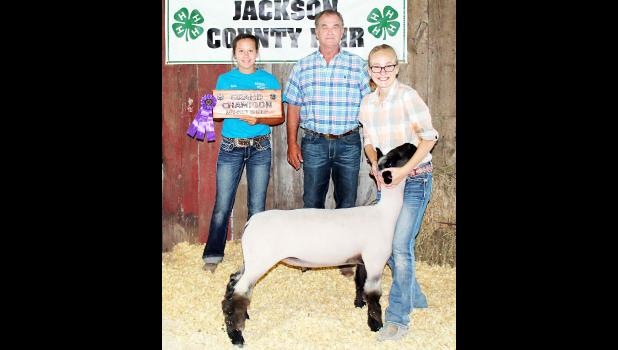 Lora Larison (right) of the Pleasant Valley Rustlers 4-H club showed the grand champion market lamb, a middleweight crossbred lamb that was also named best of its breed, at Monday's Jackson County Fair sheep and goat show. Larison is shown with sheep and goat show judge Lon James (center) and 4-H Ambassador Karlie Albright. (Photo by Brian Sanders)