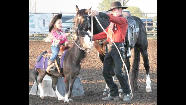 More than 2,500 people attended the Jackson County Fair Rodeo on Friday and Saturday nights at the Northeast Kansas Heritage Complex arena. The featured entertainer was Mayetta native Brian Bausch, who travels the country performing his cowboy show. In the photo above, Bausch (right) entertained the crowds with the help of his daughter Hannah, 5, and her pony. (Photo by David Powls)