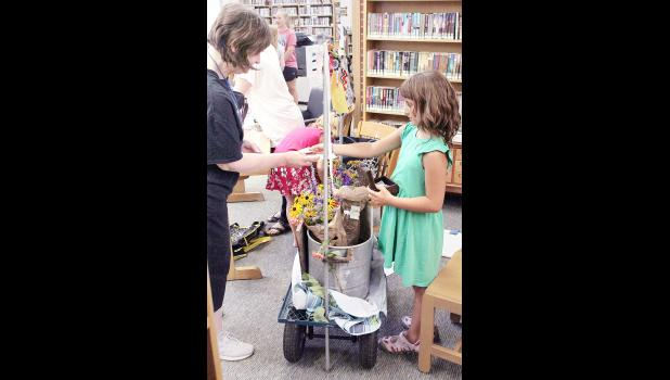 Charlotte Bear (right), a participant in Beck Bookman Library's Mid-Week Market for Junior Entrepreneurs, sold a bouquet of flowers to Karen Ford (left) of Holton during Wednesday's market, which was moved inside the library due to rain. Bear and her mother put together the bouquets and wrapped them in inspirational quotes for this year's market. (Photo by Brian Sanders)