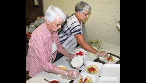 Martha Roush (left) and Brenda Fletcher were among the volunteers preparing taco salads during a fund-raising dinner for the Heart of Jackson Humane Society, held Wednesday at the Hutchins Building. (Photo by Brian Sanders)