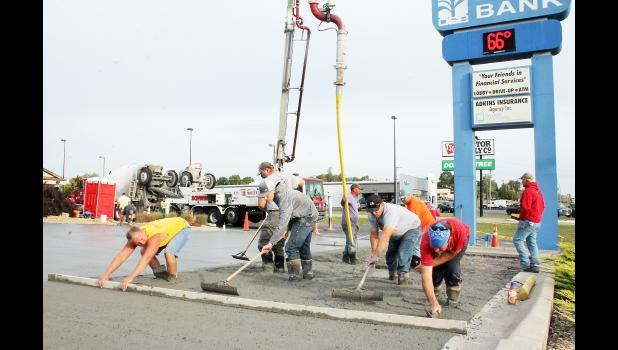 A work crew from Excell Concrete of Hoyt — including, from left to right in the photo above, Dylan McClane, RJ Bone, Jason McClane, Duane Daugherty and Jason Ogden — smoothed out wet concrete on the parking lot in front of the Denison State Bank branch building on U.S. Highway 75 on Friday, wrapping up a week of concrete work at the branch bank, according to branch manager Sherry Burns. (Photo by Brian Sanders)