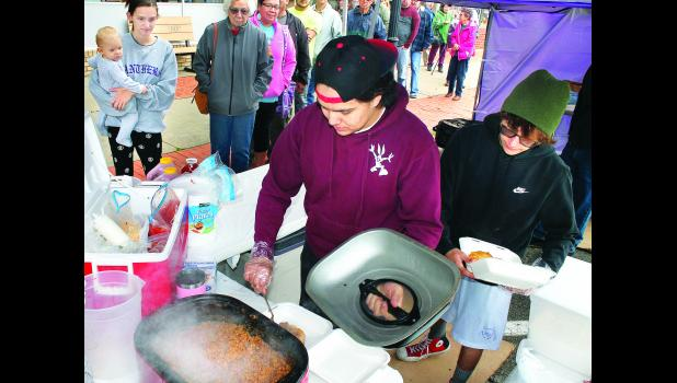 "Bryce Garrison (center) spooned chili meat into fried bread while Cody Garrison (right) brought more fried bread for preparation of ""Indian tacos"" served over lunch hour on Friday at a ""patient appreciation lunch and open house"" in celebration of Lifetime Eye Care's 10th anniversary in business on Holton's Town Square. The lunch drew a sizable crowd in somewhat chilly weather. (Photo by Brian Sanders)"