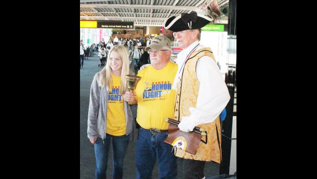"Jackson Heights senior Skyla Howe (left) and Mayetta veteran Larry Larkin (center) posed for a photo with ""town crier"" Fred Taylor, who heralded the Jackson Heights Honor Flight group's arrival at Baltimore-Washington International Airport last Wednesday. More photos from Honor Flight will be posted at this Web site. (Photo by Brian Sanders)"