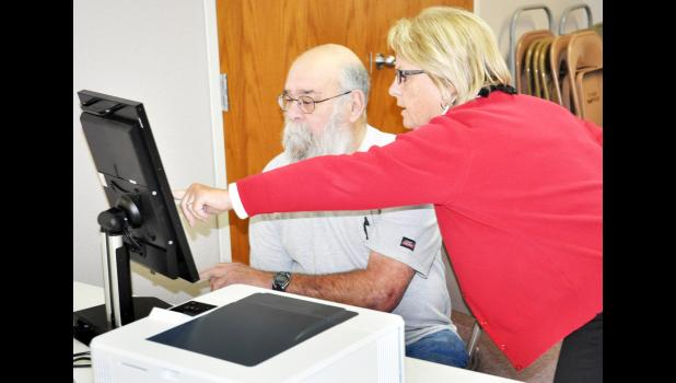 Patty Sorensen (right), polling volunteer, showed Holton resident Gary Stous how to cast his vote on a new touchscreen voting machine at the First Baptist Church in Holton Tuesday during the general election. The election had an 11.7 percent voter turnout, it was reported. (Photo by Ali Holcomb)