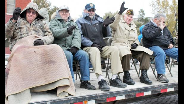 Local military veterans (from left to right) Kenny Wykert, Ed Hayes, Allen Bowser, Fred Shea and Jackie Lundin bundled up to ride around Holton's Town Square on Friday afternoon as part of the annual Veterans Day Parade. (Photo by Brian Sanders)