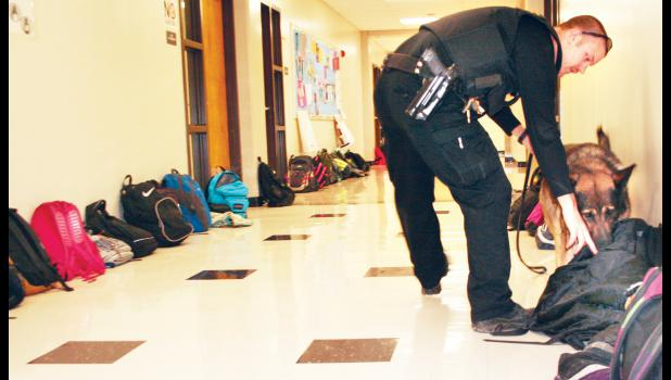 Jackson County Sheriff Deputy Travis DeBarge and his K-9 partner, Benny, are shown above searching school bags placed in the lower hallway at Royal Valley High School on Thursday. The drug dog searches are conducted at the school and the parking lot two to three times a year. (Photo by Ali Holcomb)