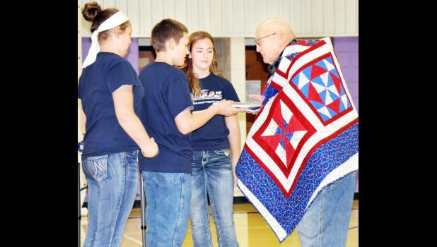 Royal Valley Middle School students (from left) Morgan Davis, Richard Zeller and Olivia Flowers-Rickle presented veteran Melvin Wells (right) of Holton with one of three Quilts of Valor during a Friday presentation at the school. (Photo by Ali Holcomb)