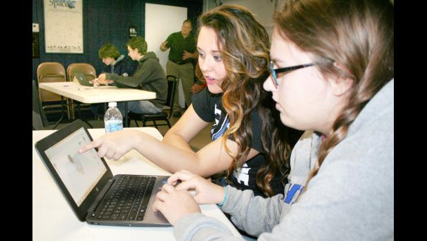 "Holton High School juniors Madi Lira (center) and April Utterback (right) used the Tinkercad computer-aided drawing program to create a Thanksgiving turkey during their participation in a Thursday morning STEM curriculum course at Banner Creek Science Center. Lira said she was ""getting a little bit frustrated"" that the turkey wasn't turning out how she expected, but Utterback added, ""this is probably one of our better ones."" (Photo by Brian Sanders)"