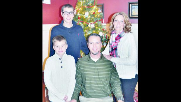 The Meerpohl family, including (clockwise from upper left) Carson, Nicole, Brian and Carter (not pictured: Ashtin Meerpohl), pose with one of a handful of Christmas trees that may be found in their home during the 2015 Christmas Homes Tour. (Photo by Ali Holcomb)