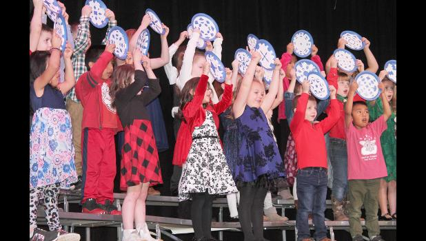 """Kindergarten students at Holton Elementary School held up paper plate """"snowflakes"""" during their Christmas concert Tuesday night in the Holton High School auditorium to help illustrate """"Snowflake, Snowflake,"""" one of eight songs the students performed. (Photo by Brian Sanders)"""