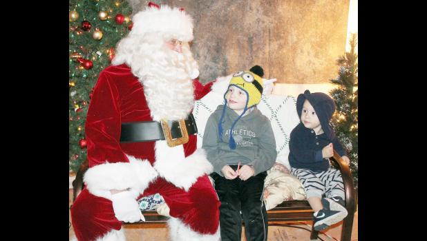 Six-year-old Bryler Brucken (center) shared his Christmas wish list with Santa Claus while Bryler's younger brother, two-year-old Treagen, waited his turn during a recent visit to Santa's Workshop. The brothers are the sons of Chad and Kayla Brucken of Holton. (Photo by Brian Sanders)