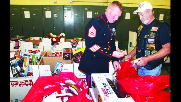 "Gunnery Sgt. Max Coons (left) of the U.S. Marine Corps and Jack Pittaway of the Holton VFW Riders stuffed red bags full of toys and other ""stocking stuffers"" at the Holton National Guard Armory on Tuesday morning in preparation for distribution through the Toys for Tots program. This is the first year that the program, involving the collection and distribution of new toys to children in need during the Christmas season, has been done in Holton, Pittaway said, but the first time has been a huge success."