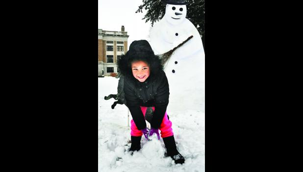 Tess Austin, 7, couldn't resist the fallen snow in front of the Jackson County Courthouse Thursday morning and decided to build a snowman. All three Jackson County school districts cancelled classes that day due to the snow.