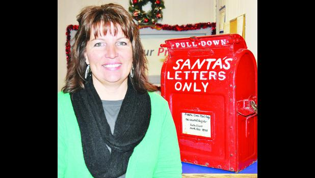 Jennifer Ingels of Holton, standing at the ready to help deliver those last-minute letters to Santa Claus, has been named the new postmaster at the Holton Post Office. She is a native of Denison and has worked for the post office since 1999. (Photo by Ali Holcomb)