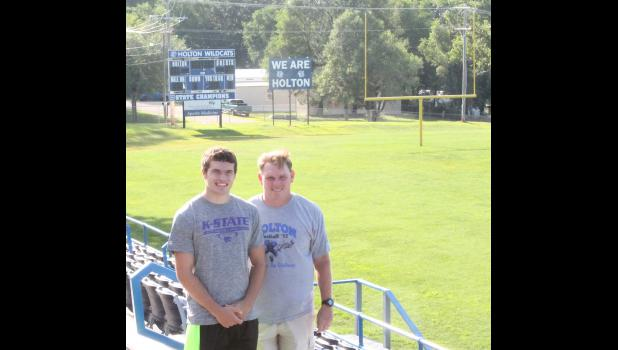 Holton High School football coach Brooks Barta (shown above, at right) stands with his son, Mason (left), in front of the field where the pair have had a lot of shared experiences. Another experience the two will share is playing college football for Kansas State, as Mason recently committed to KSU. Now, however, the two are preparing for their final season together on the HHS football field.