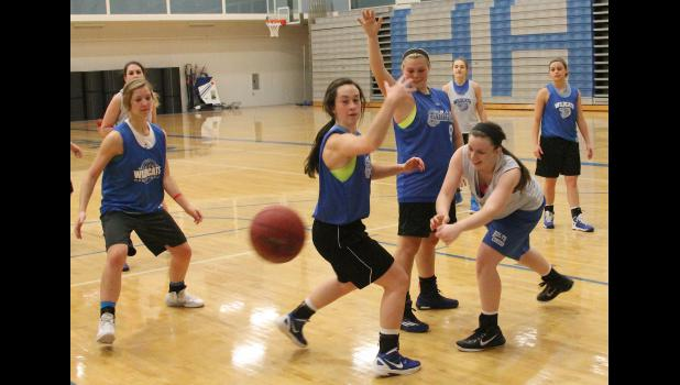 Wildcat Shari Riley (shown above, front right) passes out of the double team of teammates Quinn Holaday (middle right) and Courtney Boswell (middle) as the Wildcats worked through their offense at a recent practice.