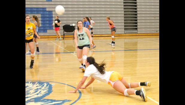 Holton's Megan Rhule (shown above, at left) and Shari Riley (middle) look on as teammate Hayley Thompson (diving, at right) lays out to save a ball during a recent practice. All three played key roles in the team's two wins to open the season on Tuesday.