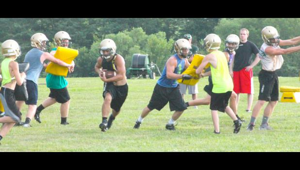 Jackson Heights running back Adam Brey (shown above, middle) shoots through a hole created by his lineman and fellow backs as the team runs through some plays at summer camp. JHHS coach Caleb Wick said the leadership of Brey and his fellow seniors will go a long way towards building this team up heading into the fall.