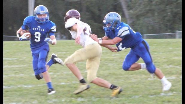 Holton running back Will Wright (shown above, at left) tries to elude a defender in early game action against Silver Lake on Friday. Wright and the Wildcat offense had a big night, but came up a little short in a 23-22 overtime loss to the Eagles.