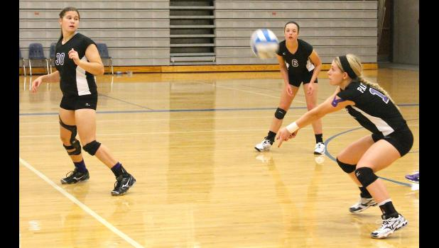 Panthers Kate Hanson (shown above, at left) and Sarah Beam (back right) look on as teammate Macy Putnam returns a serve in league competition against Holton on Tuesday night. Royal Valley fought to the end in each set, but Holton was able to pick up the sweep on its home court.