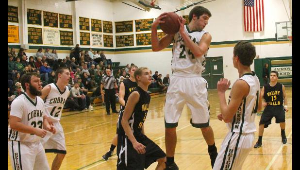 Jackson Heights' Zane Richter (shown above, second from right) comes down with a rebound early in Tuesday's NEKL contest against Valley Falls. Richter had another big night for the Cobras, but the team also showed some balance as numerous players hit key shots to give JHHS just enough separation in a 46-37 victory over the Dragons.