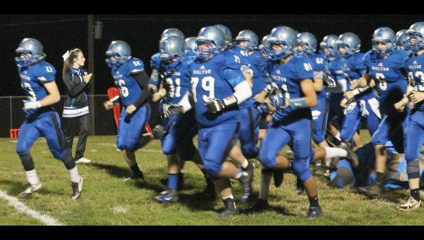 Linebacker Jordan Booth (shown above, left) leads the Wildcats onto the field as they prepare to open the Class 4A-DII playoffs against the Trojans of Osawatomie.