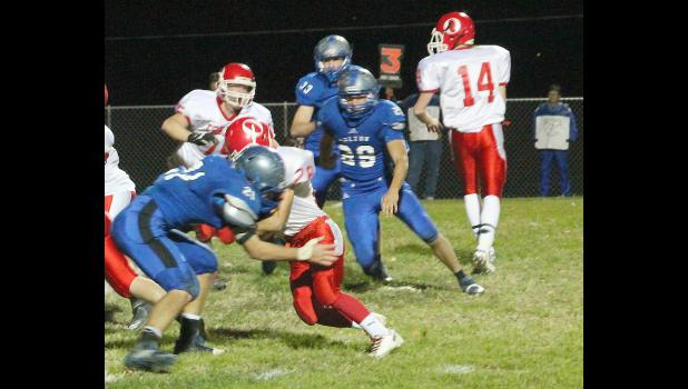 Holton linebacker Mason Barta (shown above, left) penetrates the line of scrimmage to make a stop in regional action last Friday.