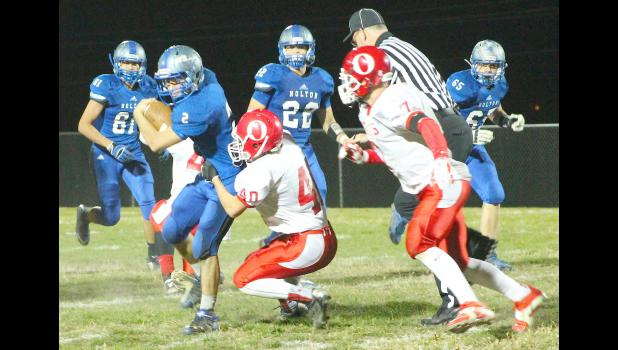 Wildcat Justin Rieschick (shown above, left) tries to break free from the grasp of a Trojan defender in regional competition. Rieschick played a hand in the team's efficient offensive night, contributing two touchdowns in the 54-8 victory.
