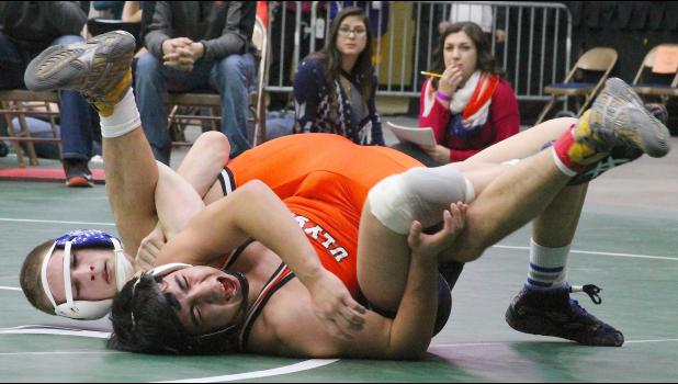 HHS wrestler Tyler Price (shown above, back left) pins his opponent in a first round match at the 4A state tournament before going on to place fourth in the 138-lb. weight class.