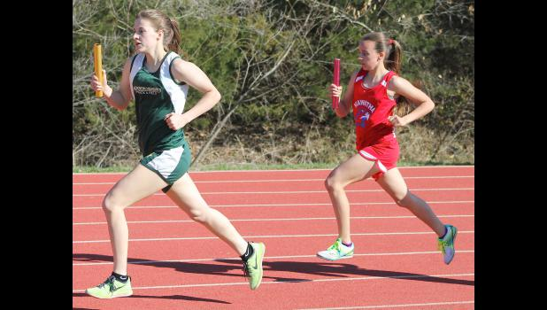 Jackson Heights' Aidan Allen (shown above, left) runs her leg of the 4x800m relay in a meet earlier this season. Allen and a number of Cobra athletes helped the team have a strong performance in Onaga last Friday and gain some momentum heading into the championship stretch.