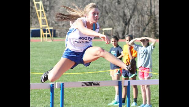 HHS hurdler Holly Karn (shown above) soars over one hurdle during the 100m race at the Holton Invitational on Tuesday. Karn got off to a good start this season, setting personal records and taking first in both the 100m and 300m hurdles at the Wildcats' home meet.
