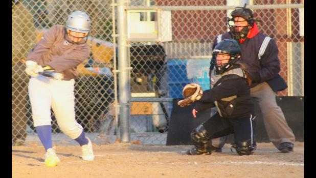 Wildcat Ali Morris (shown above, at left) puts a ball in play in the second game of a road doubleheader in Seneca last Thursday. Morris and the HHS softball team got off to a strong start in the season-opener, sweeping Nemaha Central.