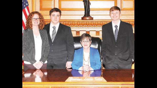 "Jackson Heights High School student Ed Mandala (second from left) and Holton High School student Aaran McAllister (right) recently met with Kansas Gov. Laura Kelly (seated) to discuss the ""Safe 75 Initiative,"" a student-led effort to encourage safety improvements along U.S. Highway 75 between Holton and the Kansas-Nebraska state line. With the students is JHHS Student Council adviser Katie Morris. (Submitted photo)"