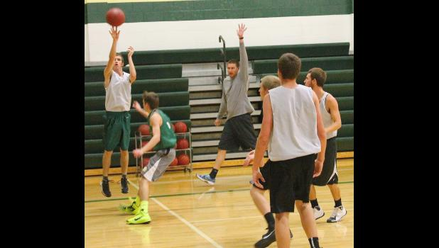 Jackson Heights' Lane Holliday (shown above, left) launches a shot over teammate Westin Jacobsen as new head coach Chris Brown (back middle) looks on and works to teach his team during  a recent practice.